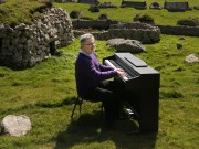 """Photograph: Times photographer James Glossop  Composer Sir James MacMillan plays songs from the album """"The Lost Songs of St Kilda"""" on the island, which is 64 kilometres west-northwest of North Uist in the North Atlantic Ocean.  Info from press release:  """"For the first time ever, we can hear the music of St Kilda – magical, melancholic folk tunes feared lost since the Scottish island dubbed 'the Edge of the World' was evacuated in 1930.  'The Lost Songs of St. Kilda' have been brought back to life on a unique new album thanks to a 73-year-old retired teacher in an Edinburgh care home, and today's leading Scottish composers including Sir James Macmillan, Craig Armstrong, Francis Macdonald and Christopher Duncan.  This new album offers a last link to life on St Kilda, the most remote spot in the British Isles (about 40 miles west of the Outer Hebrides off Scotland's north-west coast), once home to a small community of intrepid islanders who climbed its cliffs and crags in search of food.  Their folk songs were passed down from generation to generation, but have never been heard by the wider world… until now.""""  04-09-16"""